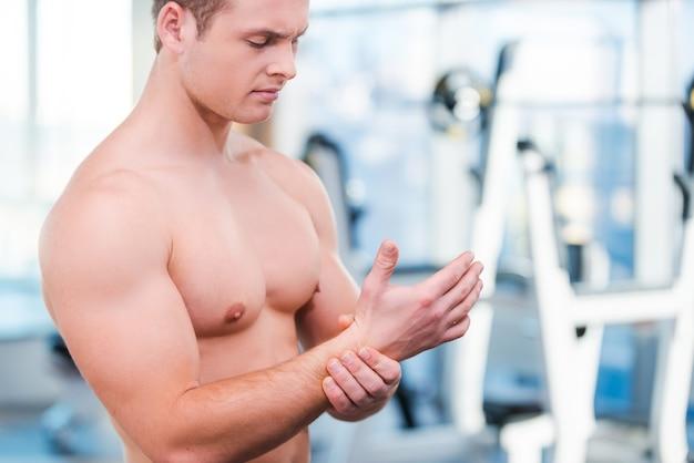 Dor após o treino. close de um homem musculoso se curvando e tocando suas costas enquanto está de pé na academia
