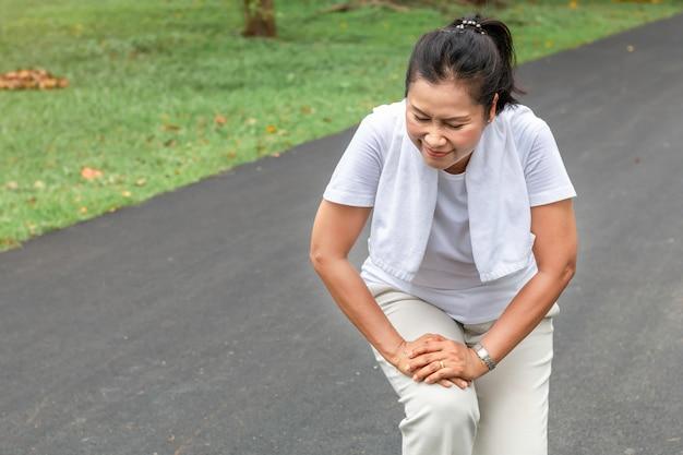 Dor asiática do pé da mulher sênior durante a corrida no parque.