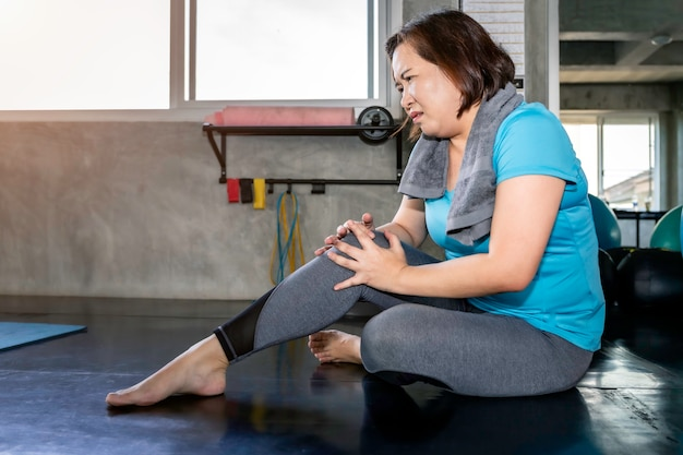 Dor asiática do pé da mulher sênior durante o treinamento no gym da aptidão.