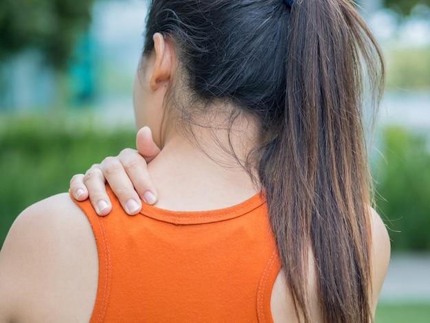 Dor da sensação da mulher do esporte do close up em seus pescoço e ombro, conceito dos cuidados médicos.