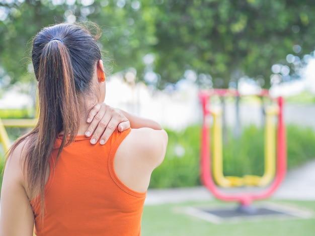 Dor da sensação da mulher em seus pescoço e ombro ao exercitar, conceito dos cuidados médicos.