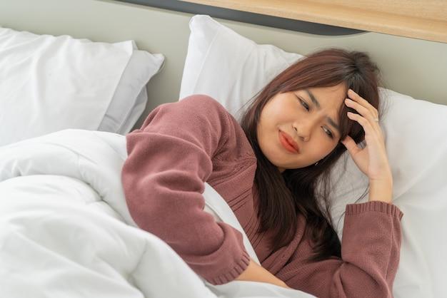 Dor de cabeça de mulheres asiáticas e dormindo na cama