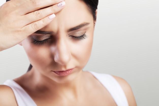 Dor de cabeça em uma jovem garota. enxaqueca. fadiga após um dia de trabalho duro. o conceito de saúde.