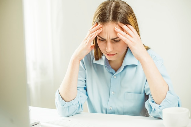 Dor de cabeça em uma jovem mulher, cansaço ou dificuldade no trabalho. retrato de uma menina triste.
