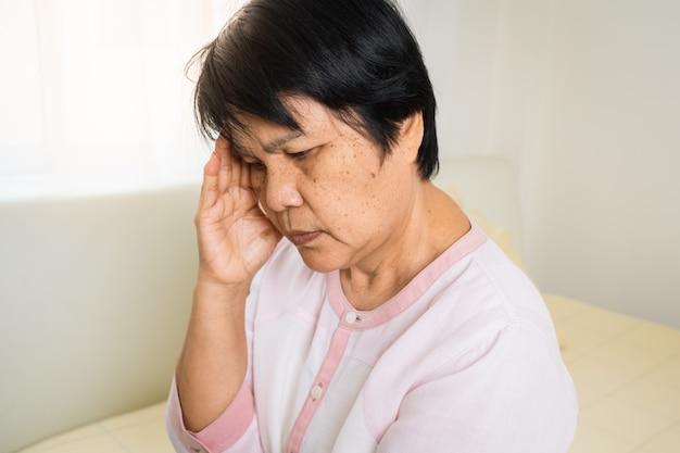Dor de cabeça, estresse, enxaqueca de mulher velha, problema de saúde do conceito sênior