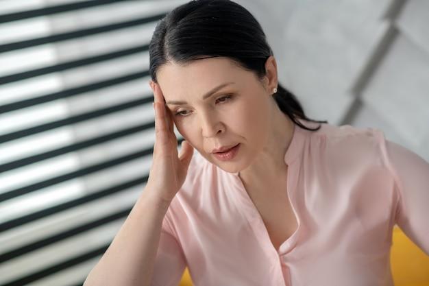 Dor de cabeça. linda mulher adulta triste, com longos cabelos escuros, segurando a mão perto da cabeça, olhando para baixo deprimido.