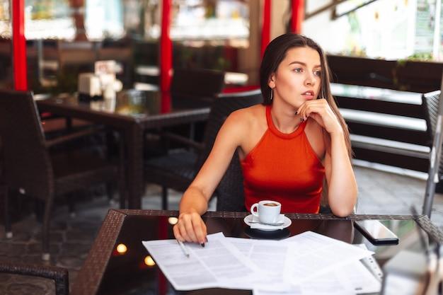 Dor de cabeça. menina sentada em um café com uma xícara de café. ambiente de trabalho. erros decepção