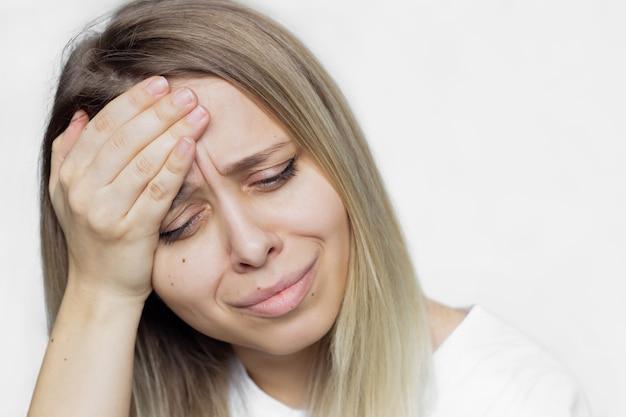 Dor de cabeça. uma jovem e bela mulher loira com dor de cabeça, segurando sua cabeça isolada no fundo branco