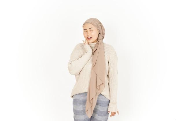 Dor de dente com mão na bochecha da bela mulher asiática usando hijab isolado no fundo branco