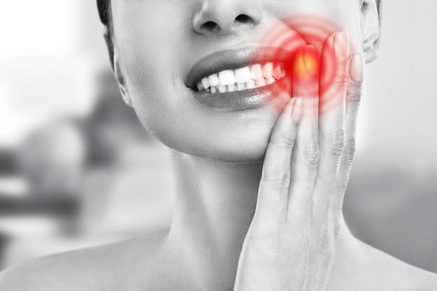 Dor de dente e odontologia. jovem sofre de dor de dentes forte, tocando a bochecha com a mão. dor de dente dolorosa feminina. conceito de cuidados odontológicos