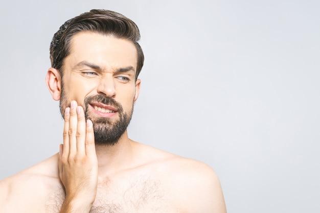 Dor de dente. jovem frustrado tocando sua bochecha