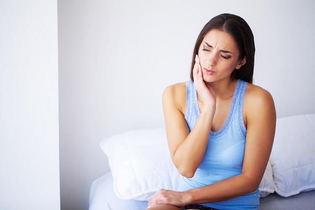 Dor de dente. mulher bonita que sofre de dor de dente dolorosa