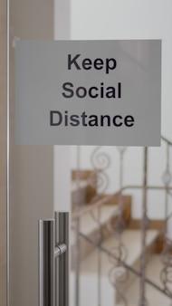 Dor de escritório de vidro com pôster para manter a distância social, escadas de escritório modernas após covid 19 pandemia de coronavírus, crise econômica global