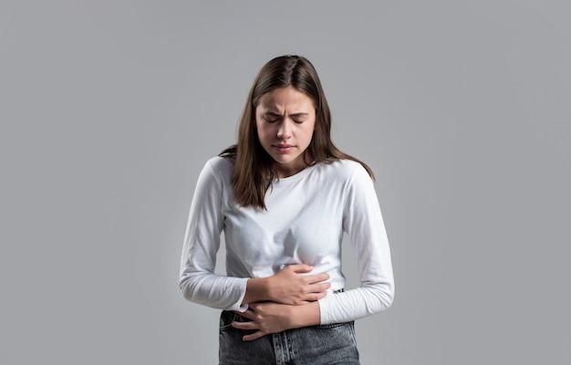 Dor de estômago da mulher. mulher tocando sua barriga. dor de estômago e outro conceito de doença de estômago. garota com dor de estômago. mulher jovem que sofre de dores abdominais.