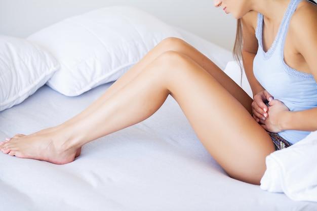 Dor de estômago. jovem mulher insalubre com dor de barriga, apoiando-se na cama em casa
