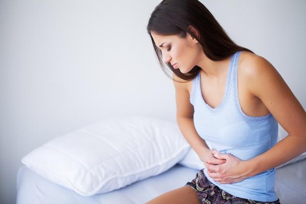 Dor de estômago. jovem mulher saudável com dor de estômago, apoiando-se na cama em casa