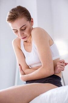 Dor de estômago. mulher doente e infeliz segurando a barriga enquanto se sente mal