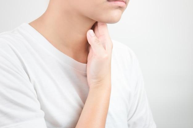 Dor de garganta. causada pelo ar seco, sem umidade. os asiáticos usam as mãos para tocar o pescoço. cuidados de saúde e conceitos médicos