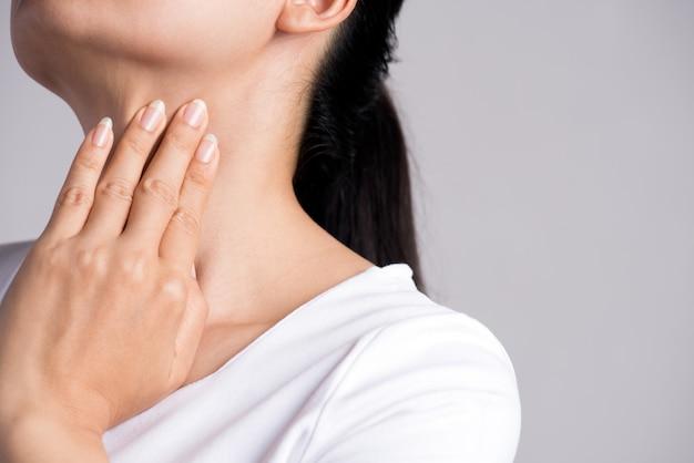 Dor de garganta. mão da mulher que toca em seu pescoço doente. cuidados de saúde e médicos.