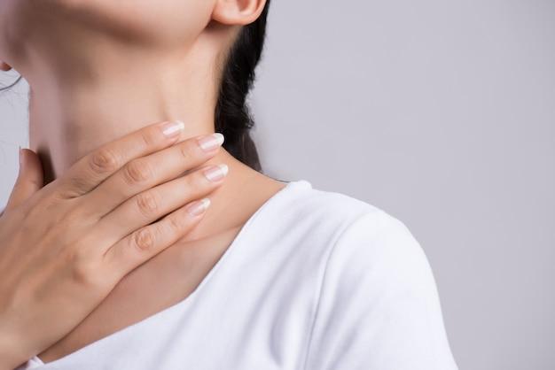 Dor de garganta. mão de mulher closeup tocando seu pescoço doente