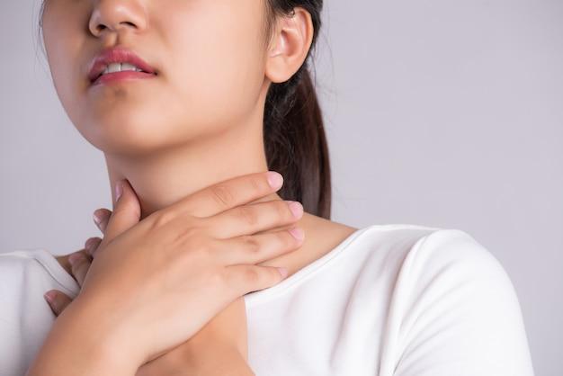 Dor de garganta. mão de mulher tocando seu pescoço doente.