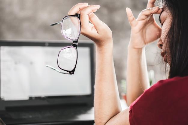 Dor de olho trabalhador mulher asiática com óculos