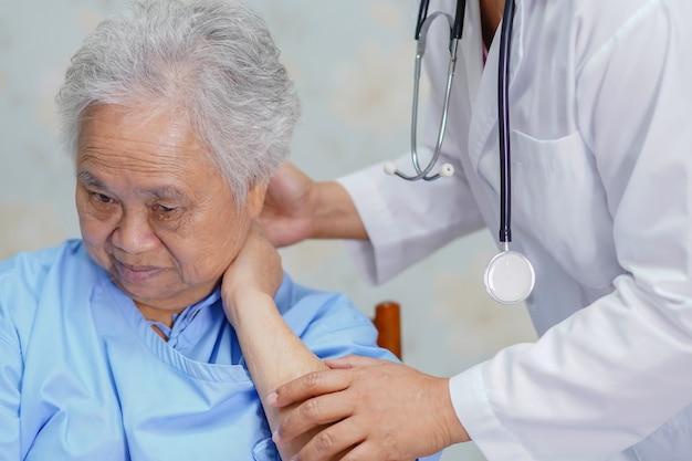 Dor de pescoço paciente da mulher sênior asiática ao sentar-se no hospital.