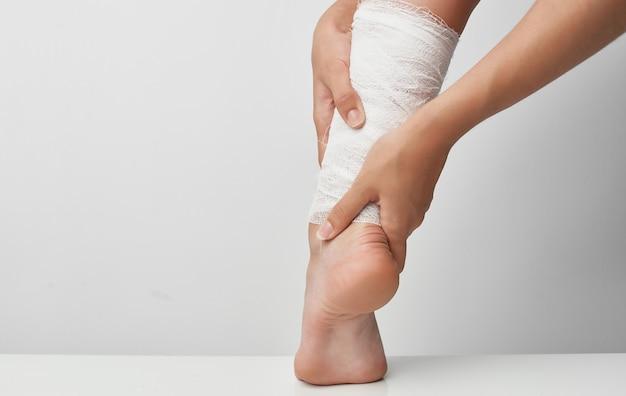 Dor de problemas de saúde de bandagem de perna feminina de ferimento de verão. foto de alta qualidade