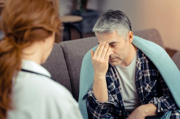 Dor desagradável. homem deprimido tocando a testa enquanto descreve seu tipo de dor ao médico