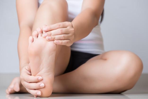 Dor do sentimento da jovem mulher do close up em seu pé em casa. conceito de saúde.