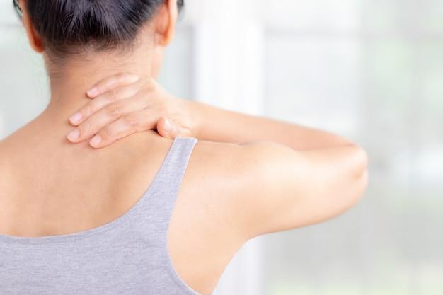 Dor e dano asiáticos do pescoço e do ombro da mulher do close up. conceito de cuidados de saúde e médico.