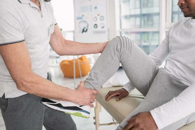 Dor forte. close de uma perna masculina sendo mostrada ao médico durante um exame médico