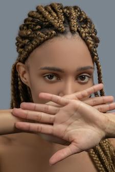 Dor interior. jovem afro-americana triste fechando a boca com as mãos cruzadas, mostrando as palmas