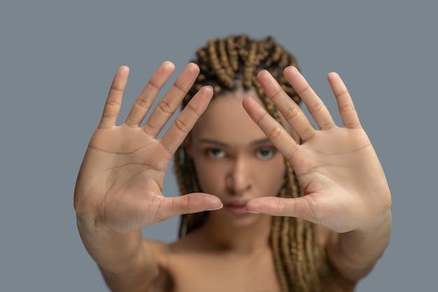 Dor interior. jovem afro-americana triste mostrando as palmas das mãos, tentando se proteger