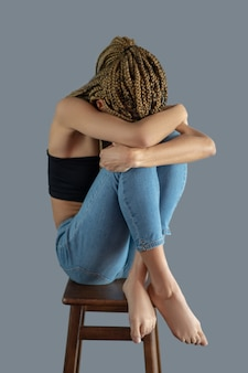Dor interior. jovem afro-americana triste sentada na cadeira com a cabeça baixa, segurando os joelhos