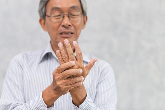 Dor na mão do idoso com dedo em gatilho ou artrite reumatóide.