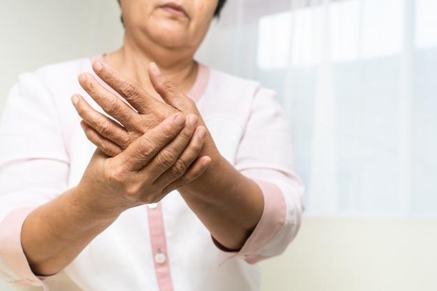 Dor na mão do pulso da mulher idosa, problema de saúde do conceito sênior