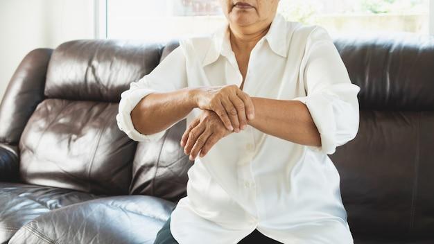 Dor na mão do pulso de uma mulher idosa, problema de saúde do conceito sênior