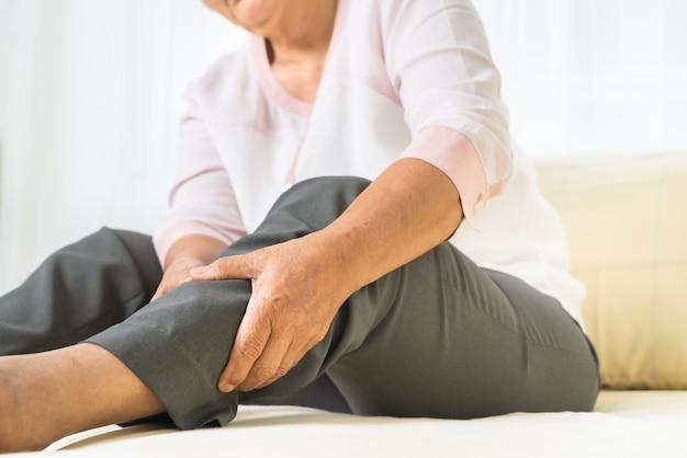 Dor na perna da mulher sênior em casa, problema de saúde do conceito sênior