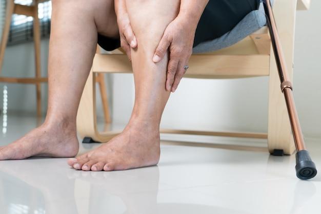 Dor na perna de mulher idosa em casa, problema de saúde do conceito sênior