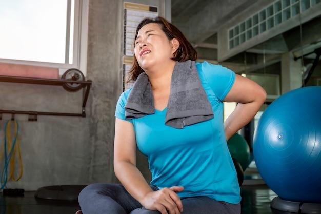 Dor nas costas asiática da mulher sênior durante o treinamento no ginásio de fitness.