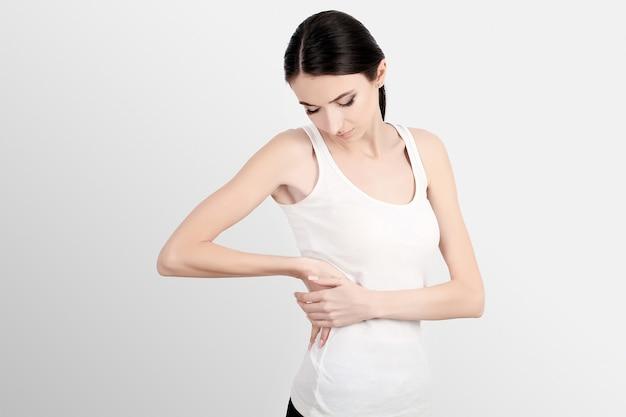 Dor nas costas, closeup de mulher bonita com dor na coluna ou rim, dor nas costas