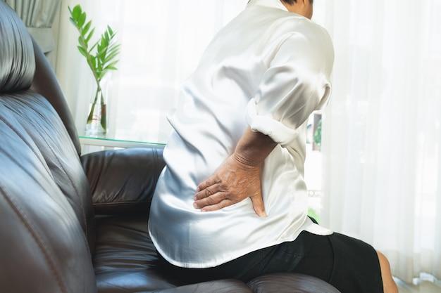 Dor nas costas da mulher idosa em casa, conceito de problema de saúde