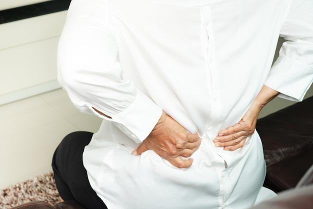 Dor nas costas de mulher velha em casa, conceito de problema de saúde