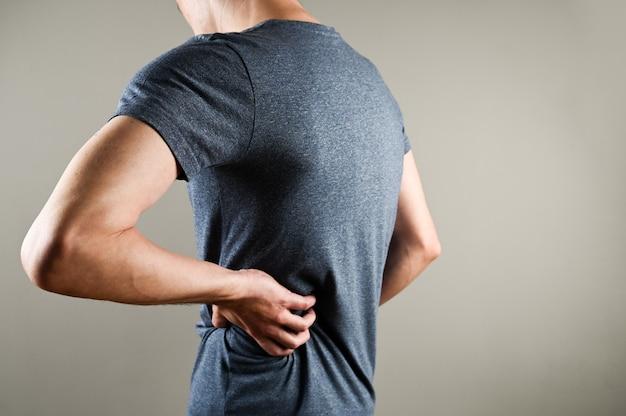 Dor nas costas e nos rins do homem. um homem de camiseta segura a mão na parte inferior das costas.