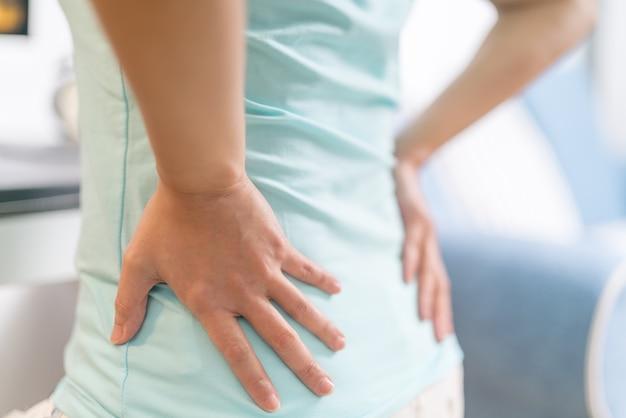 Dor nas costas em casa. as mulheres sofrem de dor nas costas. conceito de saúde e médico