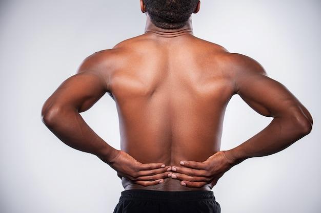 Dor nas costas. vista traseira de um jovem africano musculoso tocando seu quadril em pé contra um fundo cinza
