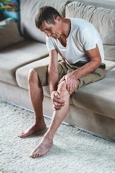 Dor nas pernas e joelhos de um idoso idoso
