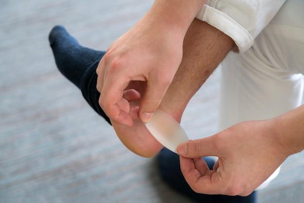 Dor no calcanhar ferido nos pés do homem causado por sapatos novos