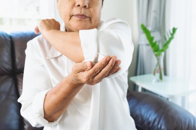 Dor no cotovelo, idosa sofrendo de dor no cotovelo em casa, problema de saúde do conceito sênior